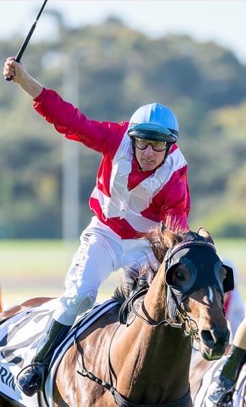 Winning jockey celebrating on thoroughbred